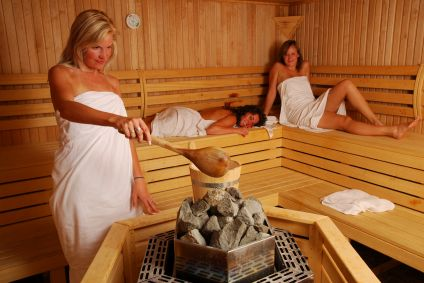 Women making steam by pouring water over sauna rocks